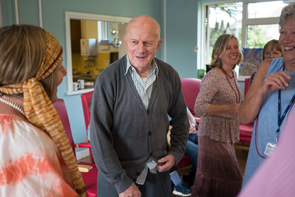 Elderly man dancing with carers
